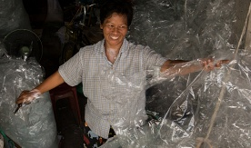 Waste picker Ananya Songsai sorts plastic at her Bangkok home. By Paula Bronstein, Getty Images