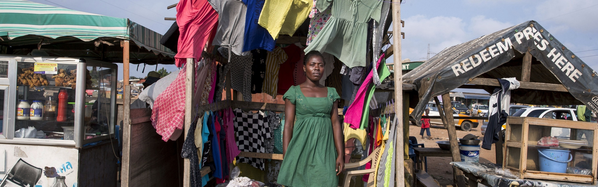 Ghanaian woman standing in clothing stall in wind