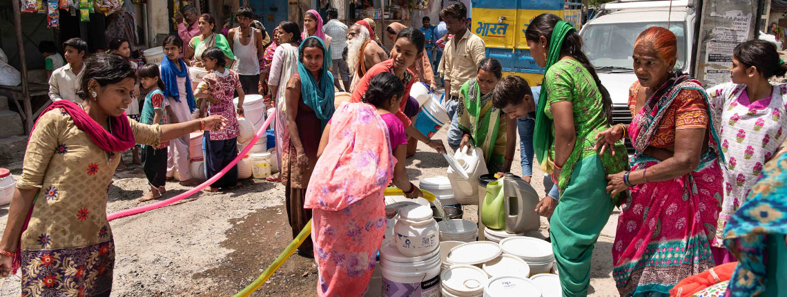 Women getting water from distribution truck in Delhi, India