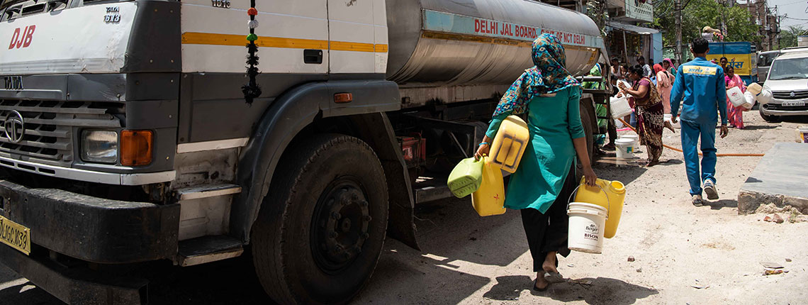 Woman getting water from distribution truck in Delhi, India