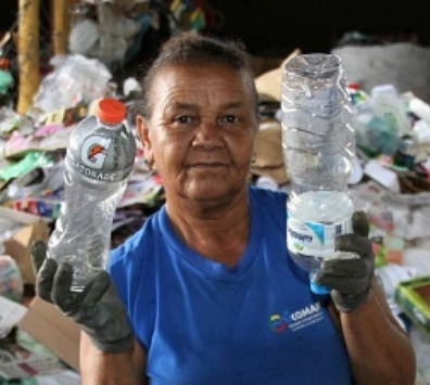 Brazilian waste picker holds up bottles
