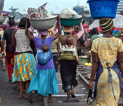 Informal Head Porters Aisha Adam (left) and Hawa Latif (right) carry goods on their heads in Kantamanto Market.