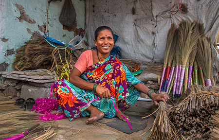 Shakuntala Rameshman makes brooms at her roadside stand on a busy street in Ahmedabad.
