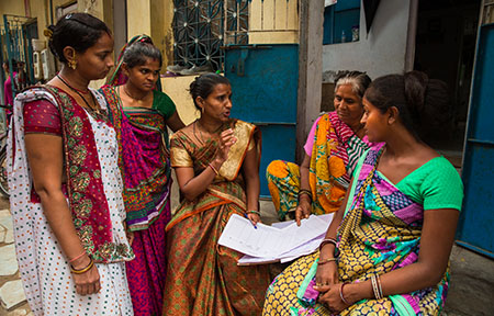 Ahmedabad, India: Neighbourhood women gather outside their homes to discuss the area upkeep and work issues.