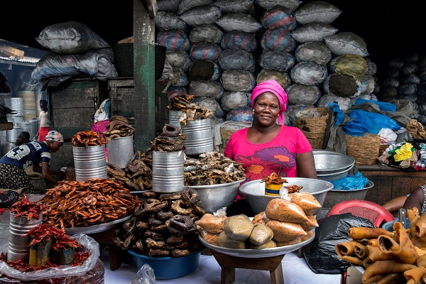 Monica Agyei in Accra stands in front of her array of foods for sale | Jonathan Torgovnik Getty Images Reportage