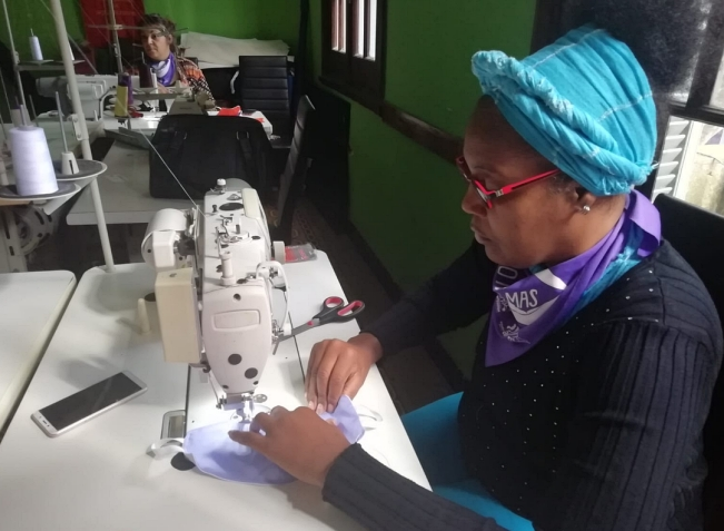 Uruguayan home-based worker sewing a mask
