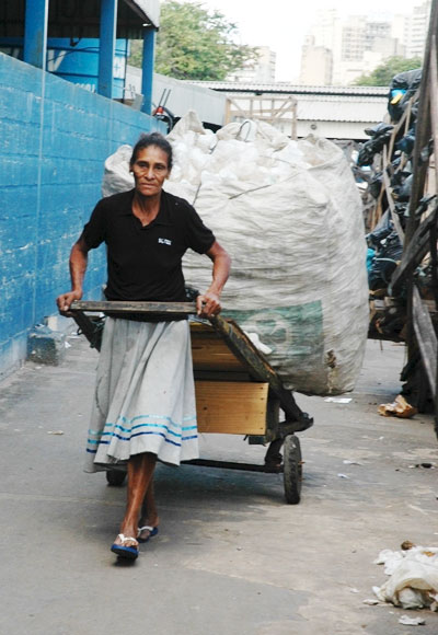 Woman waste picker pulling cart of waste in Brazil