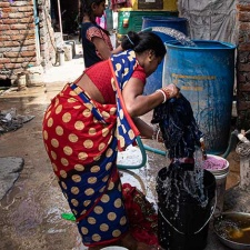 A resident of Savda Ghevra washing clothes in the narrow lane outside her home